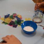 Kind bestreicht Glas mit Kleister, Windlicht basteln, Herbst, Elementar