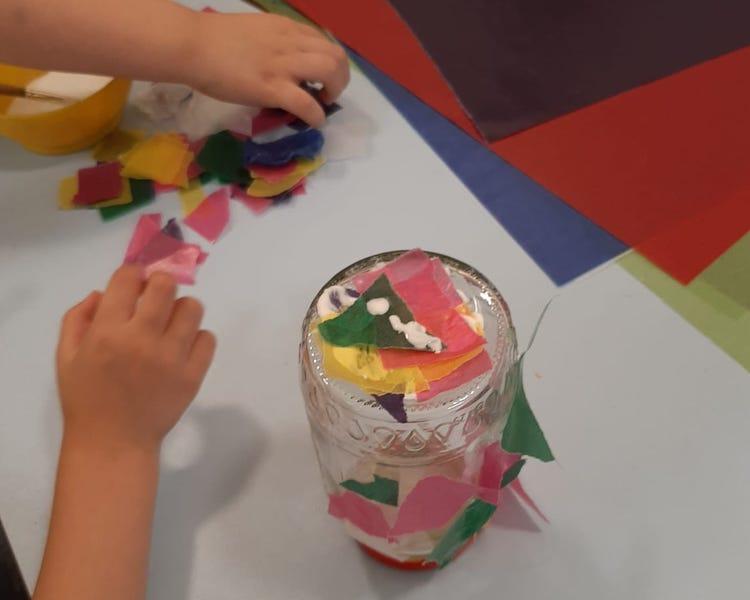 Kind beklebt Glas mit Transparentpapier, Windlicht basteln, Herbst, Elementar