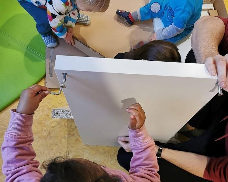Kinder bauen Schrank auf